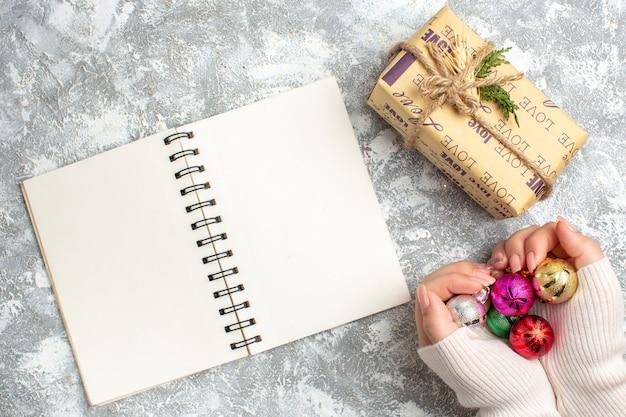 Draufsicht der hand, die dekorationszubehör des neuen jahres hält, offenes notizbuch und geschenk auf eisoberfläche