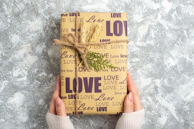 Draufsicht der hand, die ein großes verpacktes geschenk für weihnachten auf der eisoberfläche hält