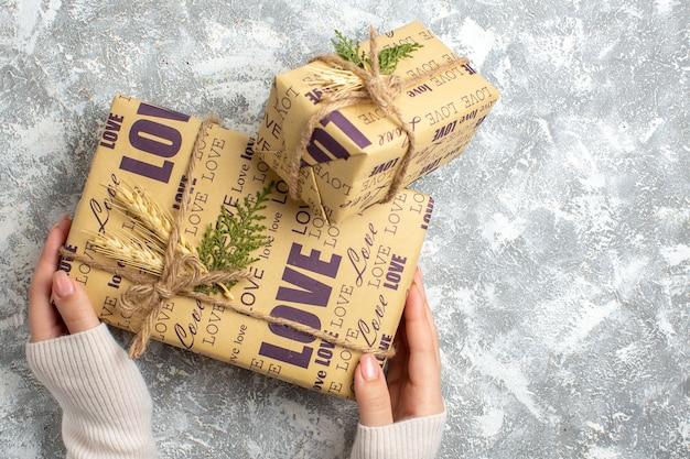 Draufsicht der hand, die ein schönes verpacktes geschenk für weihnachten auf der eisoberfläche hält