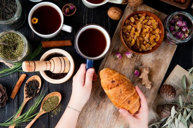 Draufsicht der hand, die eine tasse tee und ein croissant über dem holzbrett mit getrockneten rosinen in einer schüssel und verschiedenen gewürzen und kräutern auf holz hält