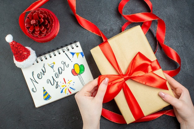 Draufsicht der hand, die einen geschenk-nadelbaumkegel mit rotem band und notizbuch mit neujahrsschrift und weihnachtsmannhut auf dunklem hintergrund hält