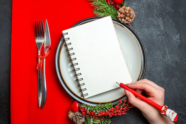 Draufsicht der hand, die einen stift auf einem spiralförmigen notizbuch auf teller mit dekorationszubehör tannenzweigen und besteck auf einer roten serviette hält
