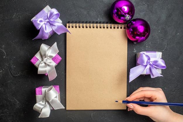 Draufsicht der hand, die einen stift und ein neues jahrdekorationsnotizbuch mit geschenken auf schwarzem hintergrund hält