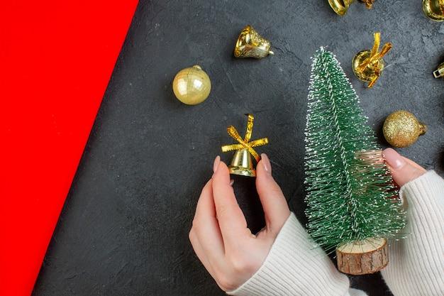 Draufsicht der hand, die einen weihnachtsbaum und dekorationszubehör auf dunklem tisch hält