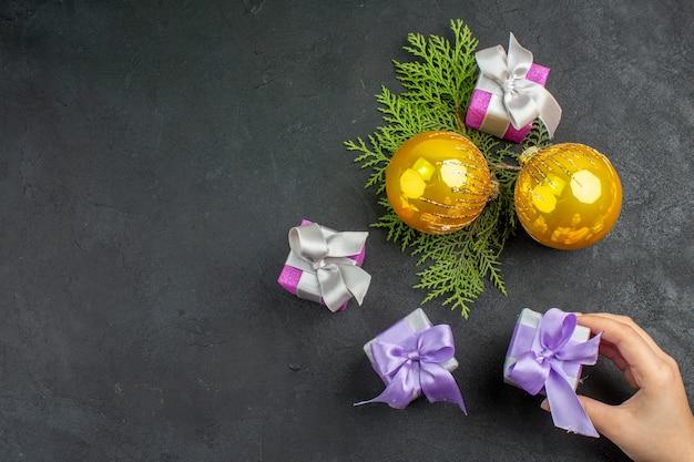 Draufsicht der hand, die eines der bunten geschenke und dekorationszubehör auf dunklem hintergrund hält