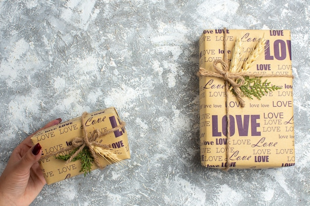 Draufsicht der hand, die eines der schönen weihnachtsgeschenke mit liebesinschrift auf der eisoberfläche hält