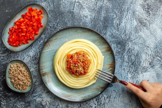 Draufsicht der hand, die gabel auf köstlichem nudelgericht auf einem blauen teller hält, der mit tomaten und fleisch zum abendessen neben seinen zutaten auf eishintergrund serviert wird