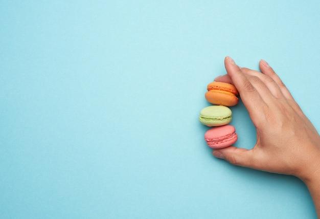 Draufsicht der hand, die macaronsplätzchen hält