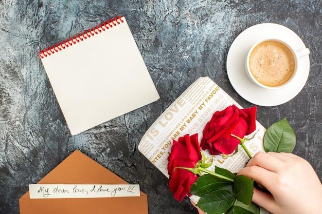 Draufsicht der hand, die rote rosen auf schöner geschenkbox und tasse kaffeeumschlag mit liebesbriefnotizbuch auf eisiger dunkler oberfläche hält