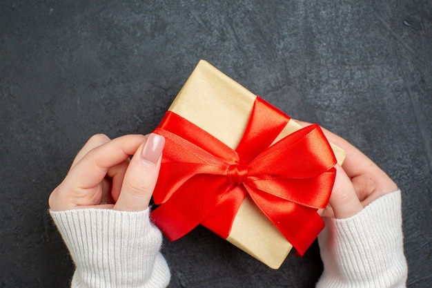 Draufsicht der hand, die schönes geschenk mit bogenförmigem band auf dunklem hintergrund hält