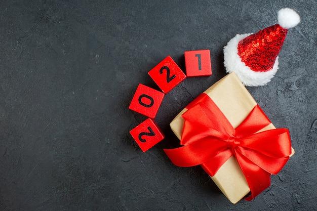 Draufsicht der hand, die schönes geschenk mit bogenförmigem band neben weihnachtsmann-hutnummern auf dunklem hintergrund hält