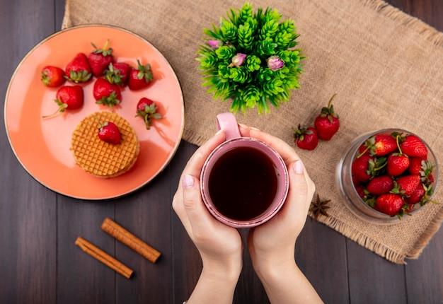 Draufsicht der hand, die tasse tee und waffelkekse mit erdbeeren in teller und schüssel und blume auf sackleinen mit zimt auf holzoberfläche hält