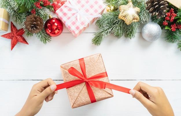 Draufsicht der hand, die weihnachts- und neujahrsfeiertaggeschenkbox mit dekorativen ornamen unboxing ist
