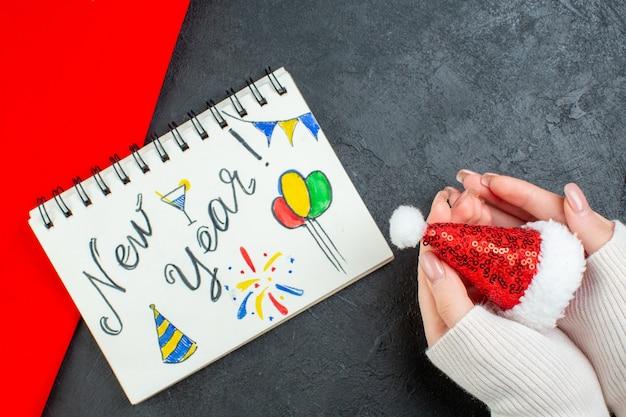 Draufsicht der hand, die weihnachtsmannhut und rotes handtuchnotizbuch mit neujahrsschrift und zeichnungen auf dunklem hintergrund hält