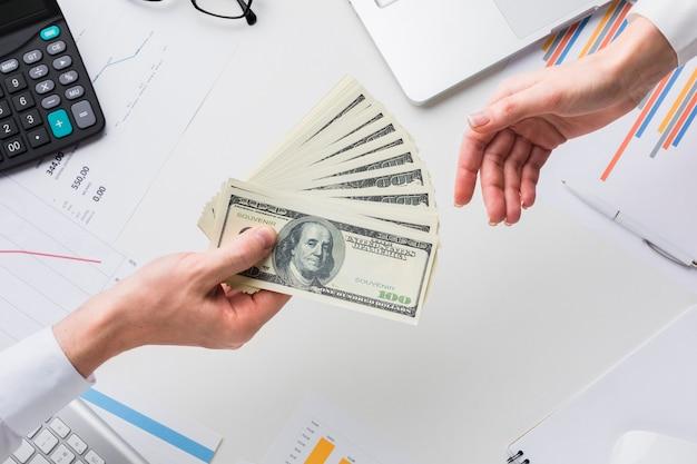 Draufsicht der hand geld über schreibtisch halten