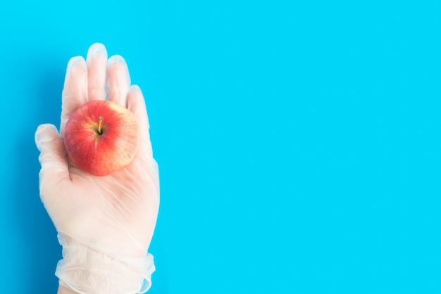 Draufsicht der hand im gummihandschuh hält roten apfel auf dem blauen hintergrund mit copyspace. konzept der sicheren lieferung