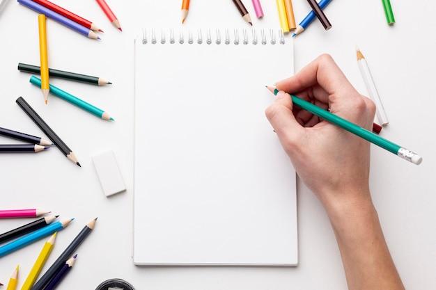 Draufsicht der hand mit bleistift auf notizbuch