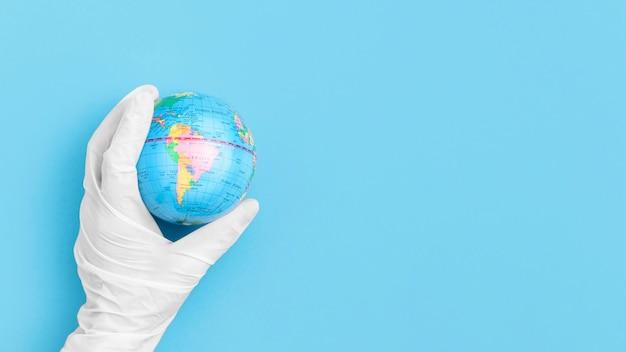 Draufsicht der hand mit dem chirurgischen handschuh, der globus hält