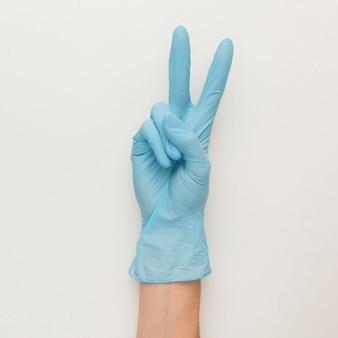 Draufsicht der hand mit handschuhen, die friedenszeichen machen