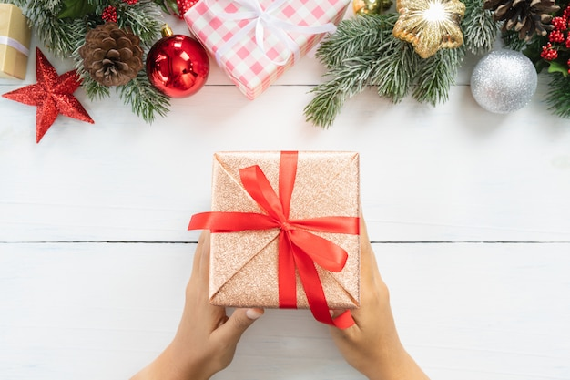 Draufsicht der hand weihnachts- und neujahrsfeiertaggeschenkbox mit dekorativer verzierung halten
