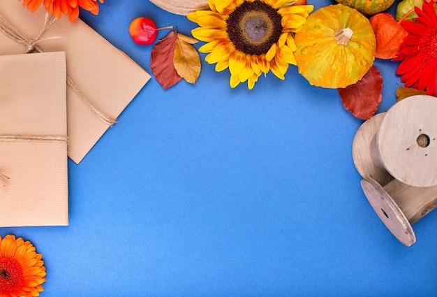Draufsicht der handgemachten geschenkbox, der gelben und orange blumen und der kürbisse auf blauem hintergrund. leere grußkarte für kreative arbeit. flach liegen