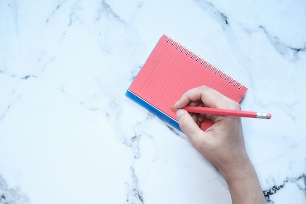 Draufsicht der handschrift der frauen auf notizblock.