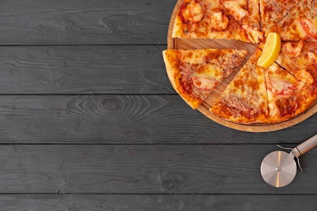 Draufsicht der heißen pizza auf schwarzem holztisch