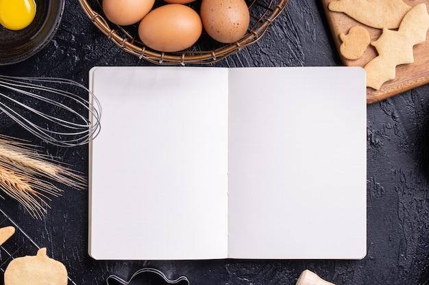 Draufsicht der herstellung von halloween-desserts durch lesen des kochbuchs