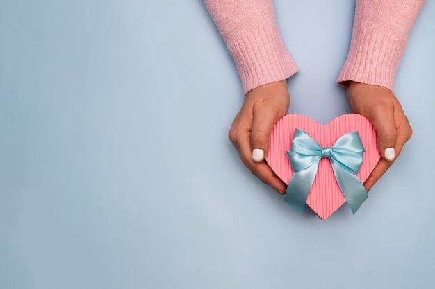 Draufsicht der herzförmigen geschenkbox in den weiblichen händen auf blauem hintergrund mit kopienraum