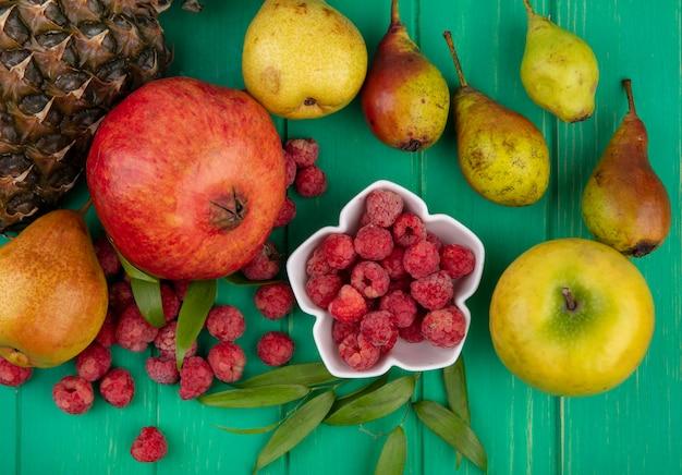 Draufsicht der himbeeren in der schüssel mit granatapfel-ananas-pfirsich und apfel mit blättern herum auf grüner oberfläche
