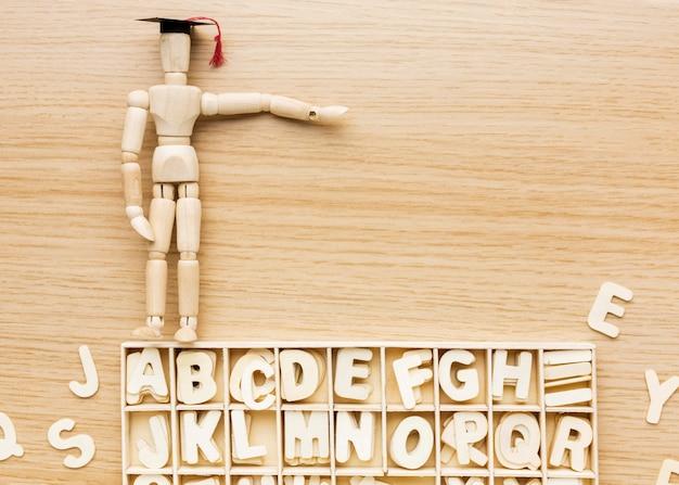 Draufsicht der hölzernen figur mit akademischer kappe und alphabet