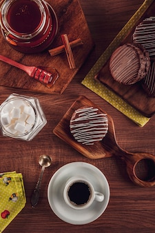 Draufsicht der honigplätzchenschokolade bedeckt auf dem holztisch mit kaffee-, honigbienen- und zuckerwürfeln - pã £ o de mel