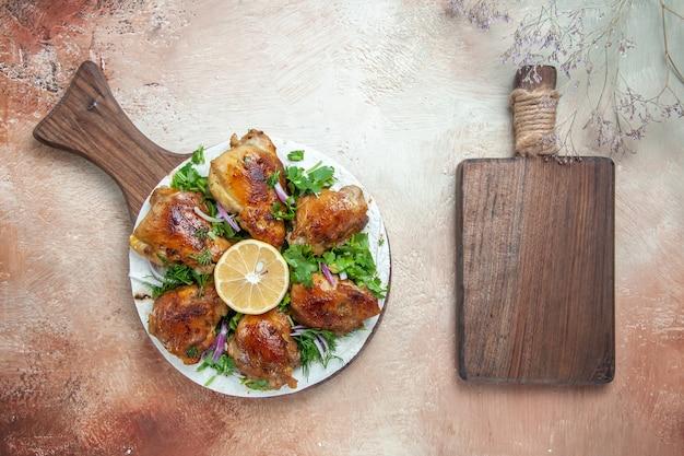 Draufsicht der huhn-hühnerkräuter-zwiebel-zitrone auf dem brett neben dem holzbrett