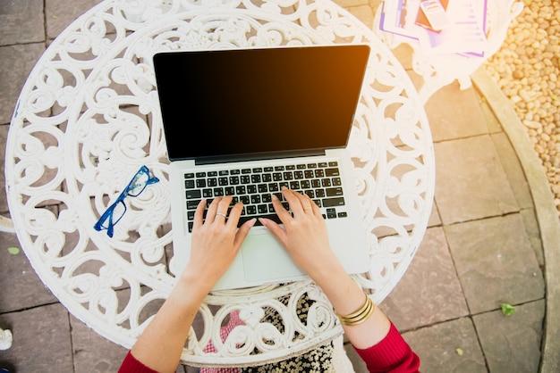 Draufsicht der jungen arbeitenden frau, die laptop verwendet und jahresberichtsdokument bei der arbeit liest. geschäftsfrau, die an ihrem schreibtisch arbeitet.