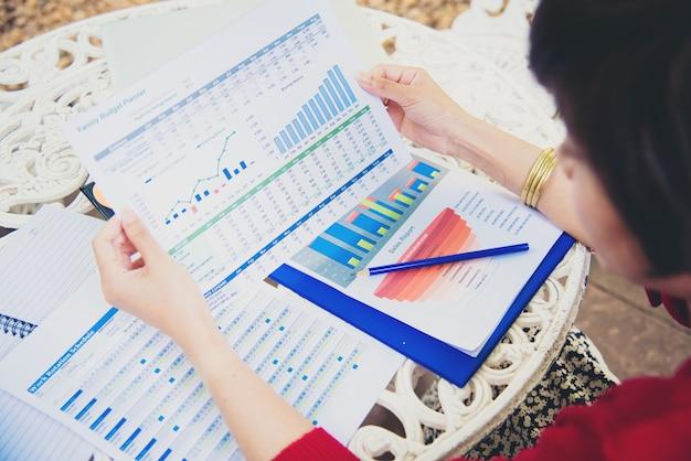 Draufsicht der jungen arbeitenden frau, die laptop verwendet und jahresberichtsdokument bei der arbeit liest.