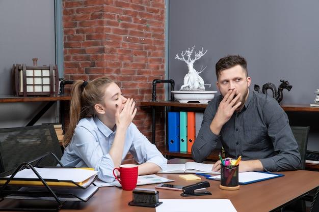 Draufsicht der jungen arbeiterin und ihres männlichen mitarbeiters, die am tisch gähnend in der büroumgebung sitzen