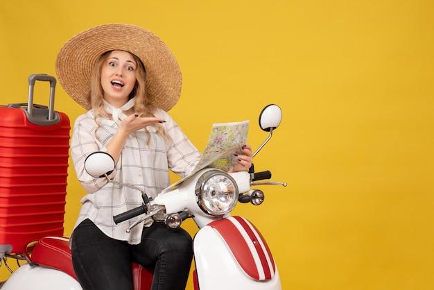 Draufsicht der jungen frau, die hut trägt und auf motorrad sitzt und karte mit lächelndem gesichtsausdruck auf gelb zeigt