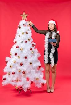 Draufsicht der jungen frau in einem schwarzen kleid mit weihnachtsmannhut und verzieren des neujahrsbaums