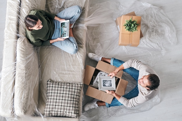 Draufsicht der jungen frau mit tablette und ihrem ehemann mit bild im rahmen, der vor einander sitzt und in der neuen wohnung plaudert