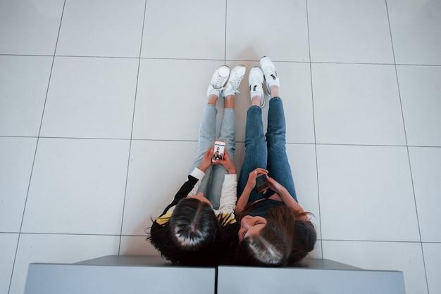 Draufsicht der jungen leute in der freizeitkleidung, die im modernen büro arbeiten