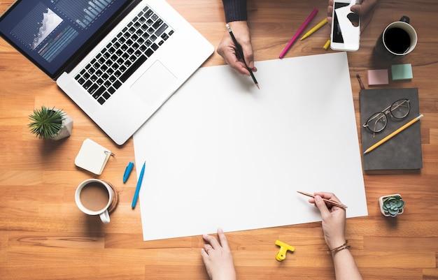 Draufsicht der jungen person, die auf tabelle mit weißem raumhintergrund arbeitet
