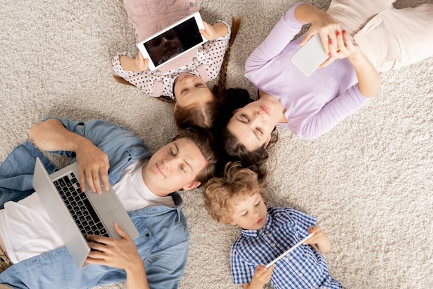 Draufsicht der jungen vierköpfigen familie, die auf dem boden liegt und in mobilen geräten rollt, während sie zu hause ruht