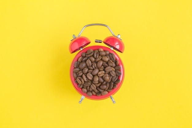 Draufsicht der kaffeebohnen auf dem zifferblatt des roten weckers in der mitte des gelben hintergrunds