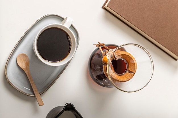 Draufsicht der kaffeetasse mit chemex und buch