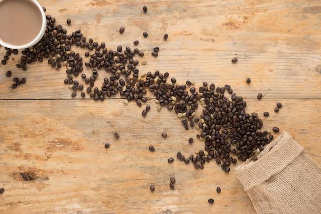 Draufsicht der kaffeetasse mit den gerösteten und rohen kaffeebohnen, die vom sack auf tabelle fallen