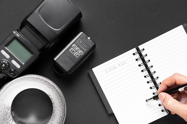 Draufsicht der kamera und des notizbuches auf schwarzem hintergrund