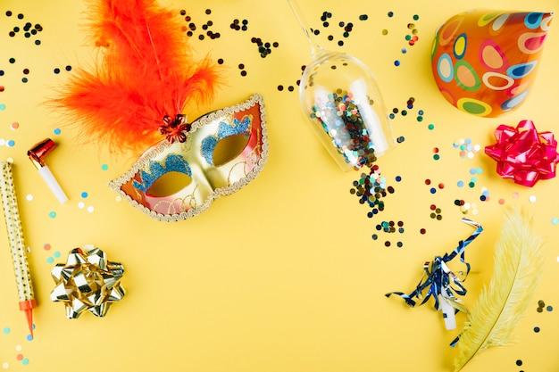 Draufsicht der karnevalsmaske mit dekorationsmaterial und über gelbem hintergrund