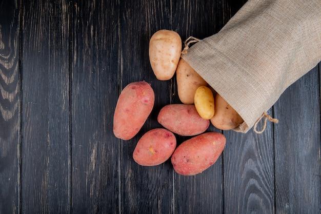 Draufsicht der kartoffeln, die aus dem sack auf holz mit kopierraum verschüttet werden