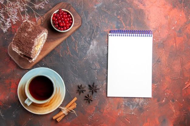 Draufsicht der keksrolle mit tasse tee auf dunkler oberfläche