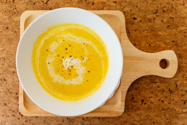 Draufsicht der klassischen pürierten kürbis-suppe, die mit milch übersteigt